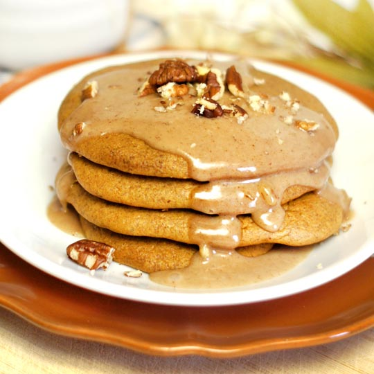 stack of pumpkin pancakes on a plate with maple glaze and crushed pecans on top