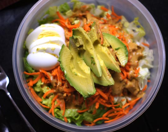 salad in a bowl with sliced egg and avocado on top