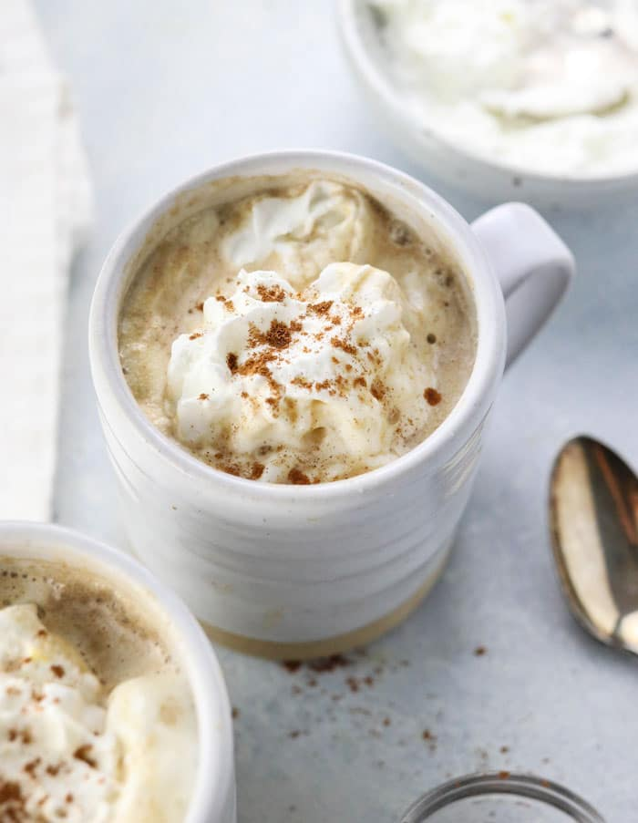 healthy pumpkin spice latte in white mug with coconut whipped cream