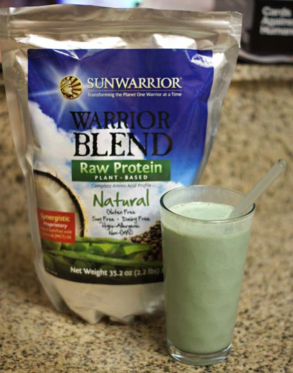 bag of sunwarrior raw protein and a smoothie in a glass next to it