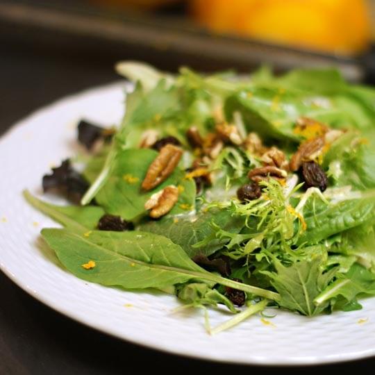 salad on a plate with sweet orange vinaigrette on top