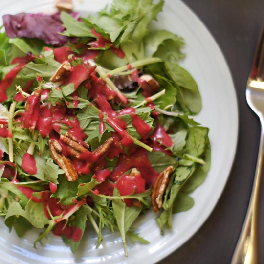 plate of salad with leftover cranberry dressing on top