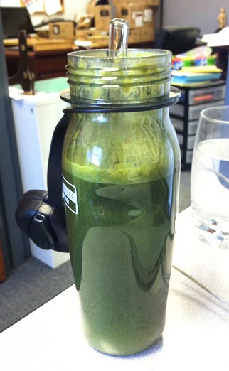 green smoothie in a water bottle and a straw