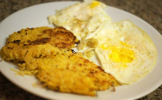 hash brown casserole on a plate with two fried eggs