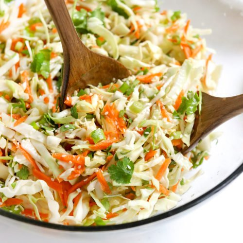 cabbage salad in bowl with tongs