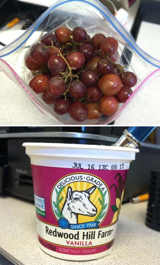 bag of red grapes and a container of vanilla yogurt
