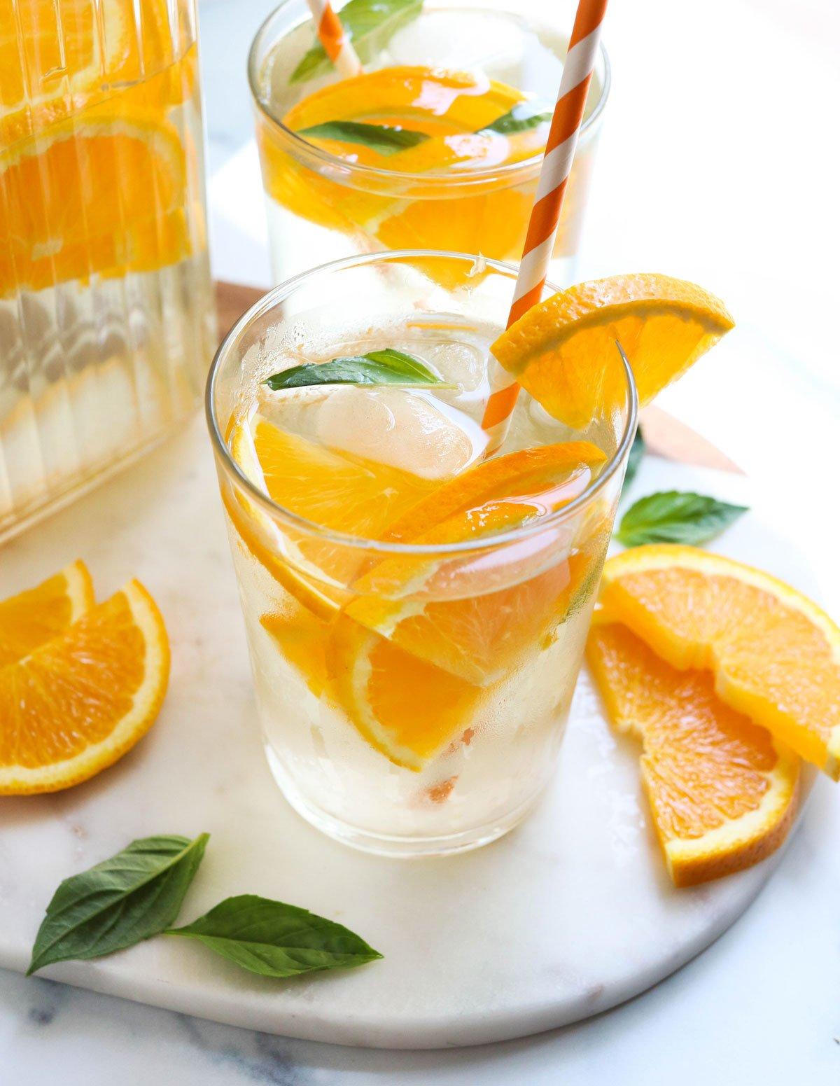 orange infused water with extra orange slices on marble
