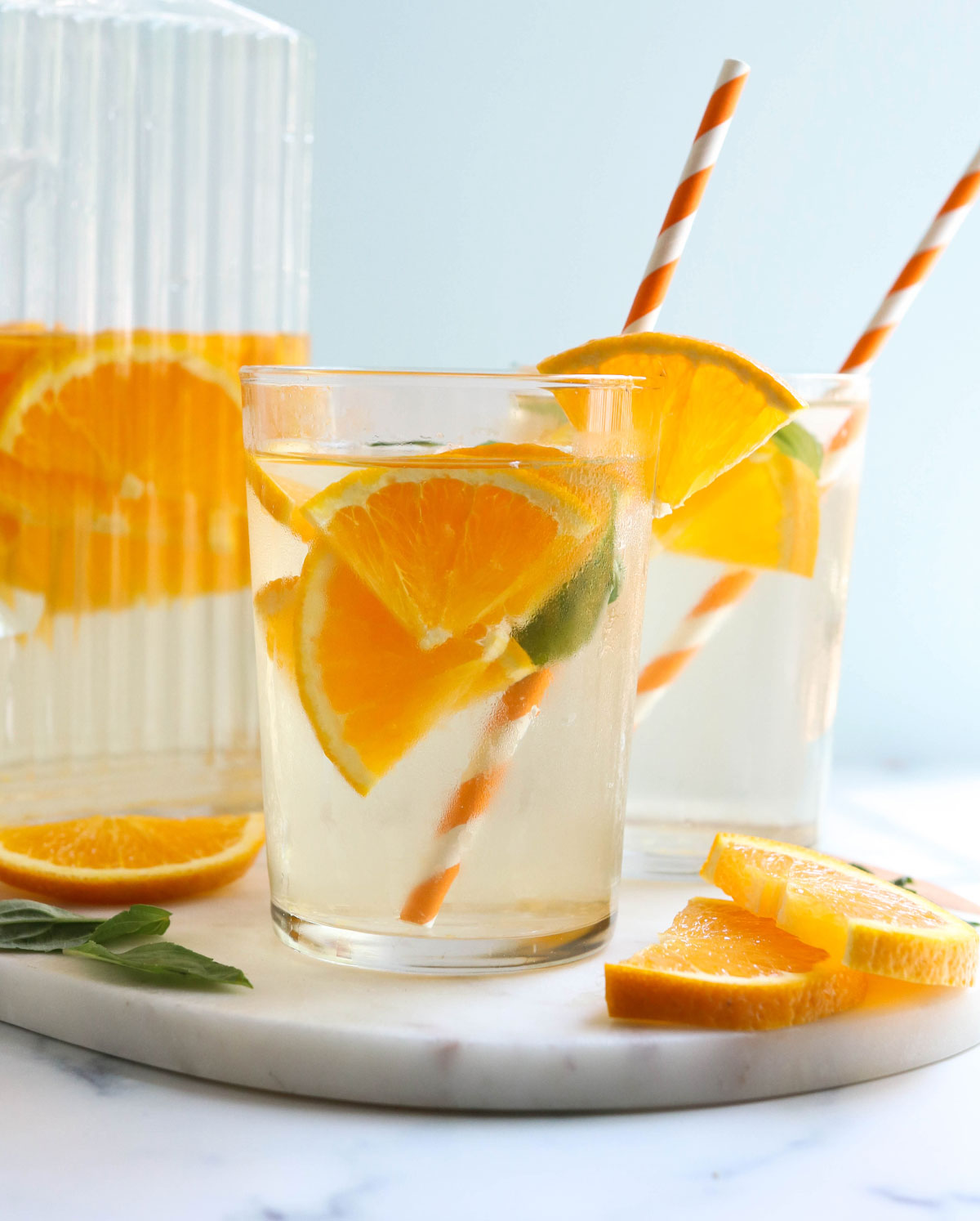 two glasses of water with orange slices