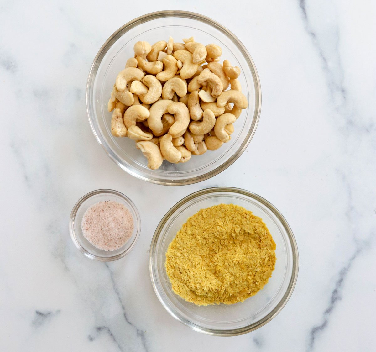 cashews nutritional yeast and salt in glass bowls