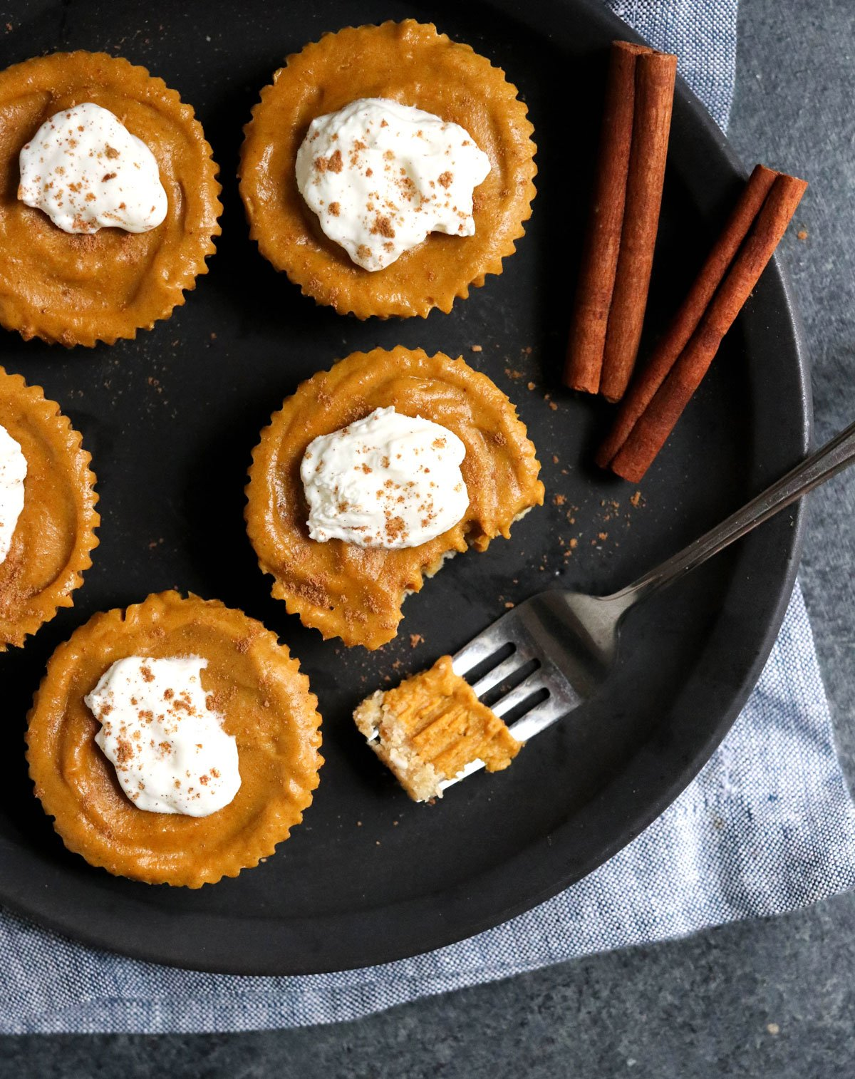 small pumpkin tarts overhead on black plate