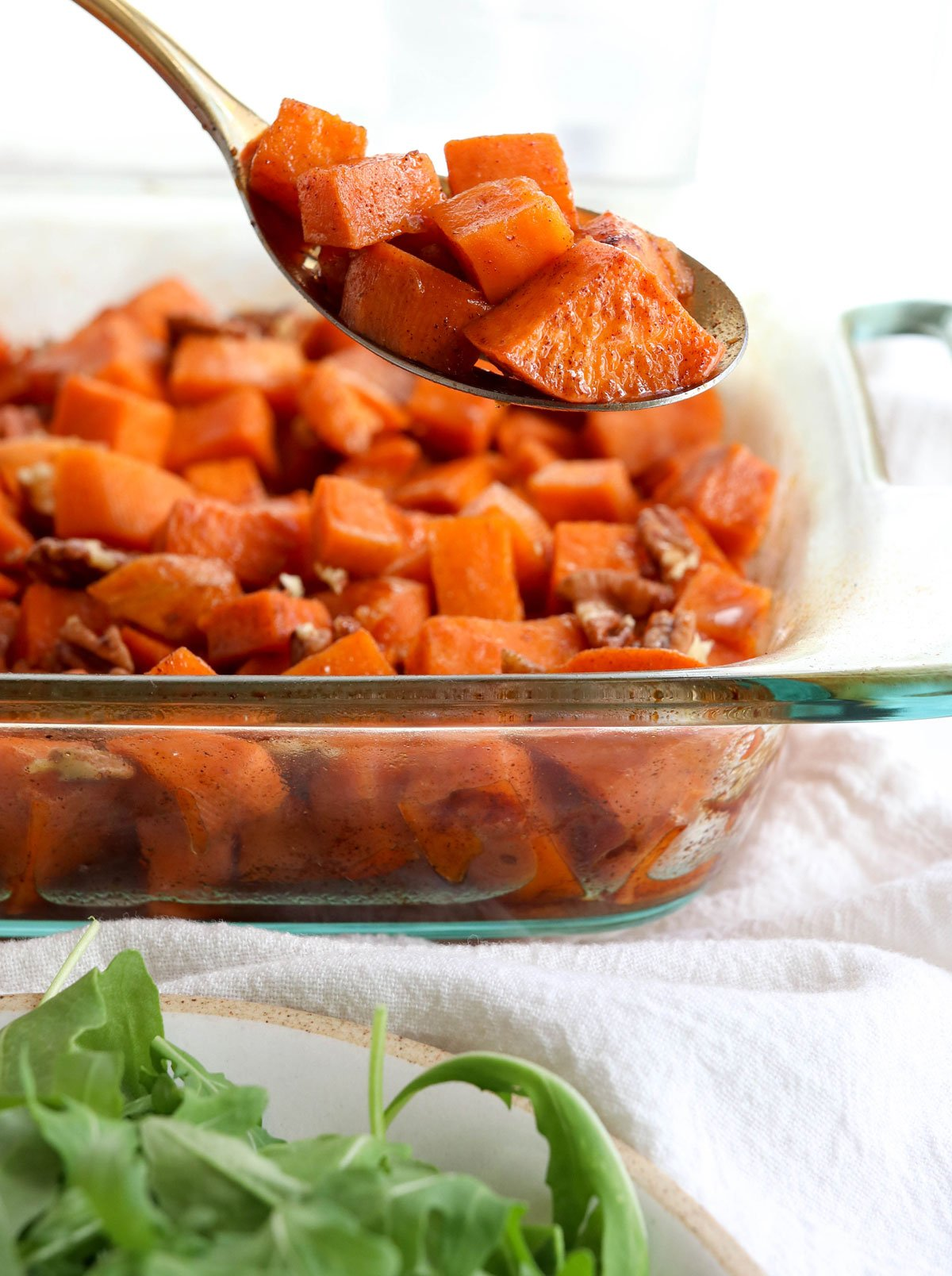glazed sweet potatoes lifted up on spoon