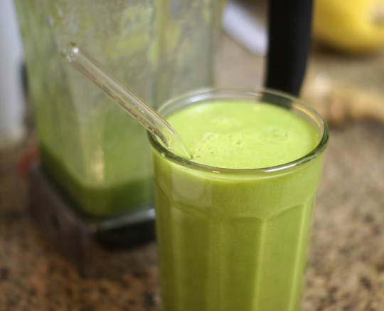 green smoothie in a glass with a straw