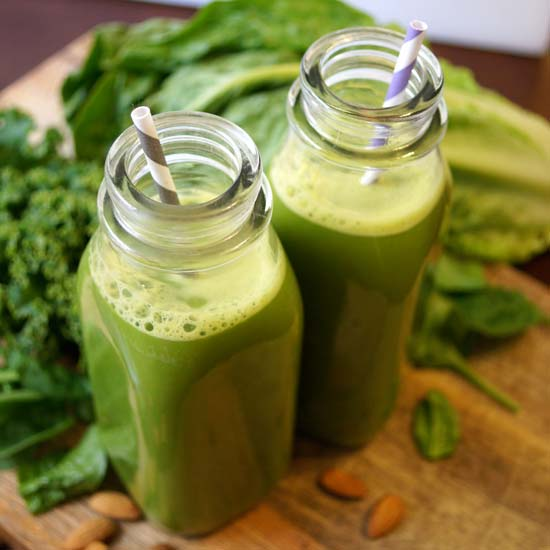 green milk in two glass bottles with straws