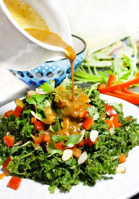 pouring spicy asian peanut sauce over salad