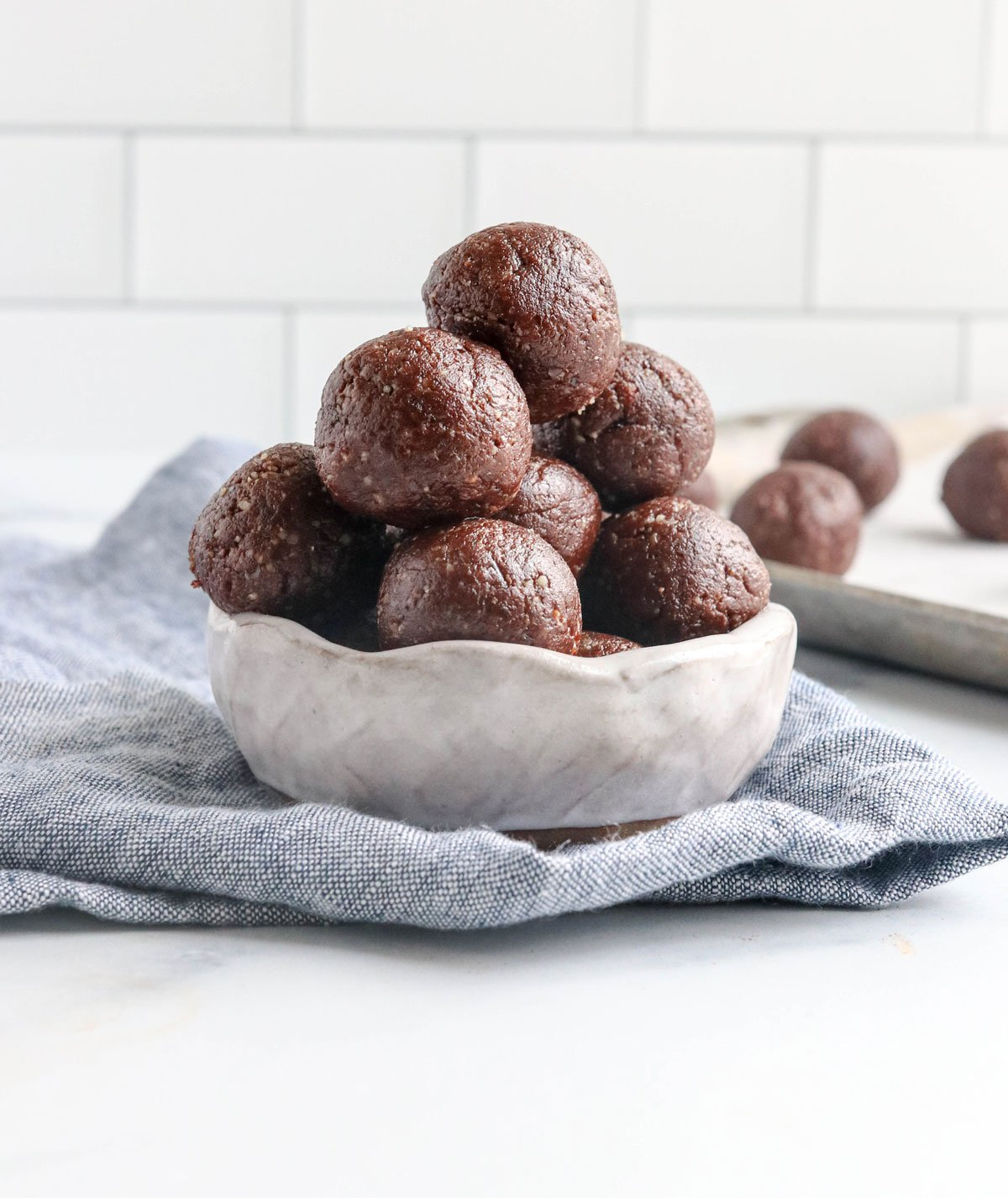chocolate date balls in white bowl