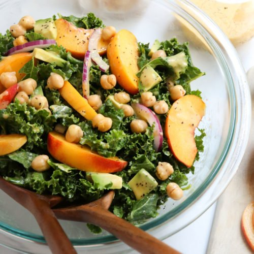 kale and peach salad with serving tongs