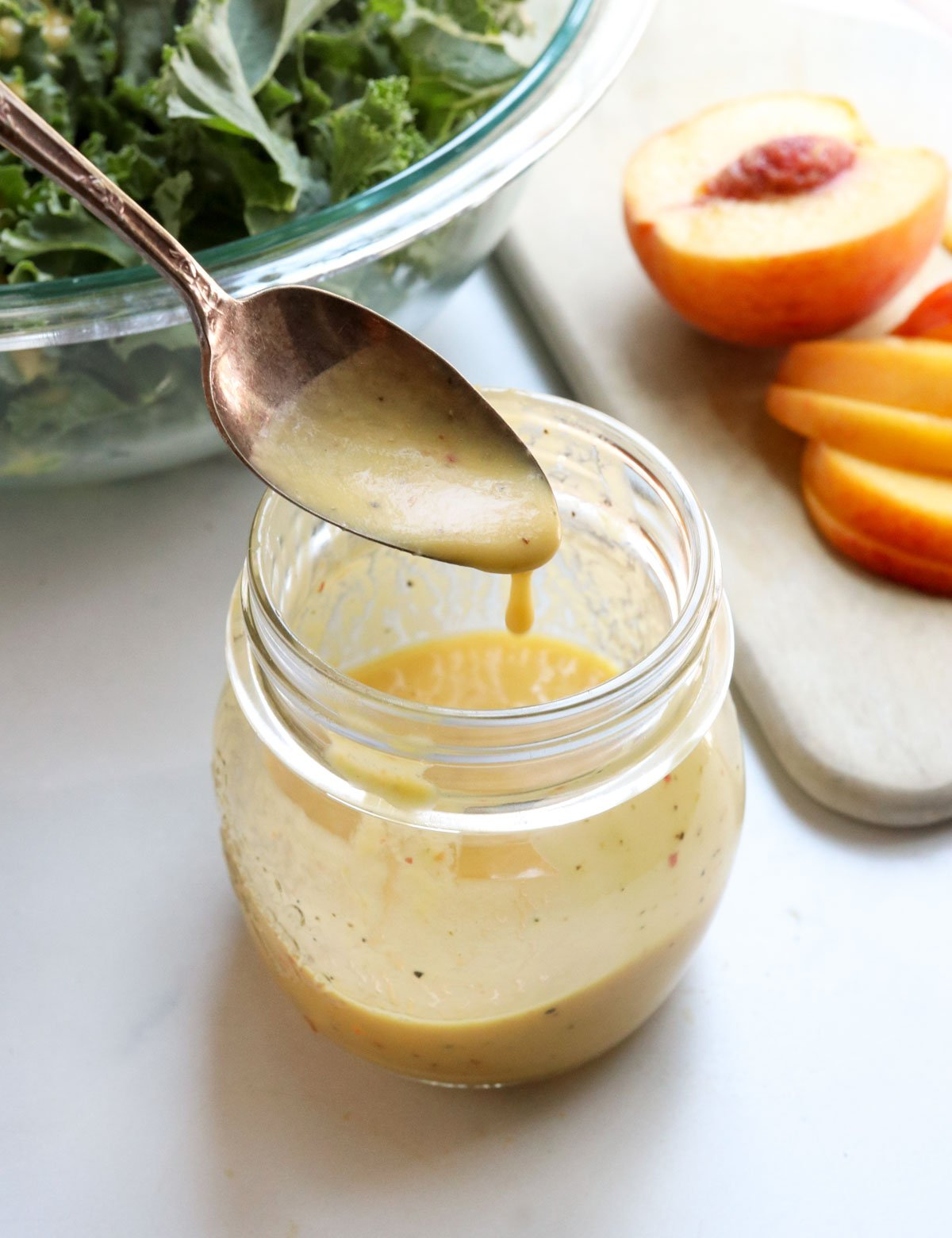 peach dressing dripping off of a spoon