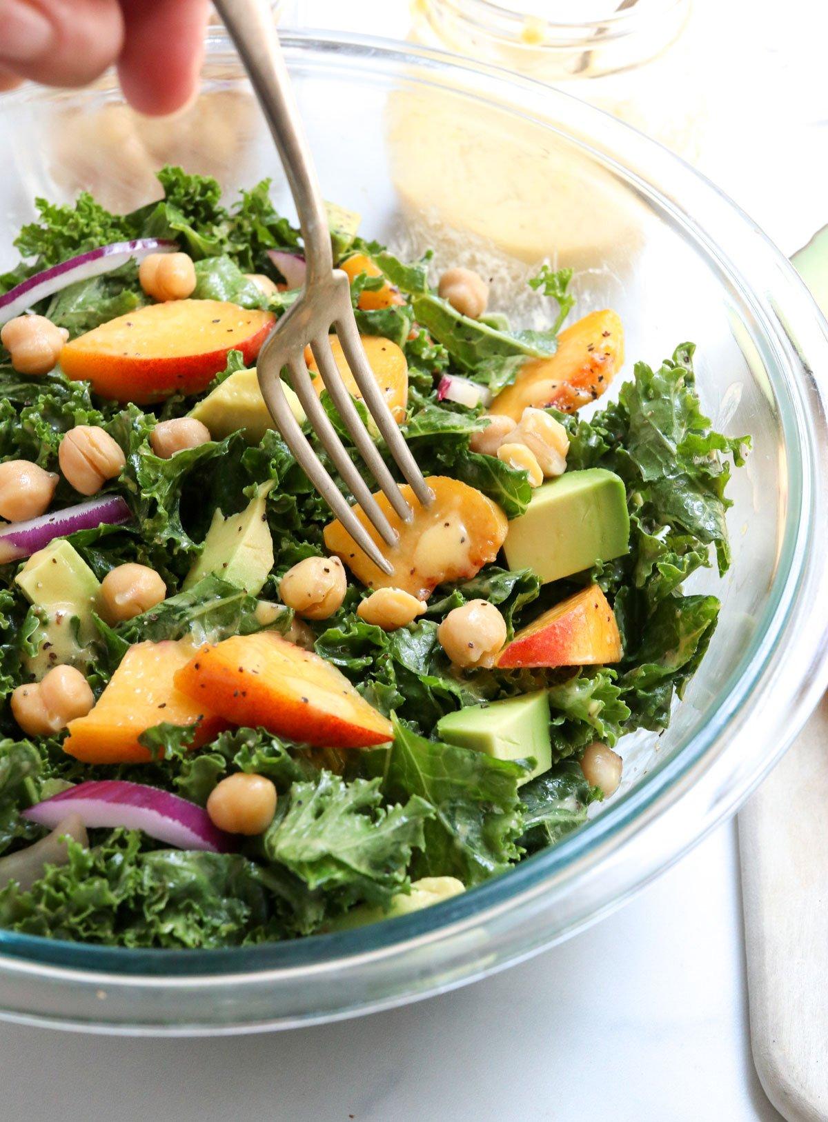fork digging into peach salad