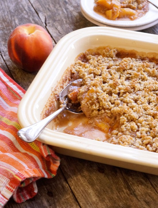 peach crisp in a baking dish with a serving spoon