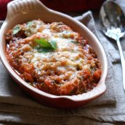 Baked vegetable marinara in red casserole dish