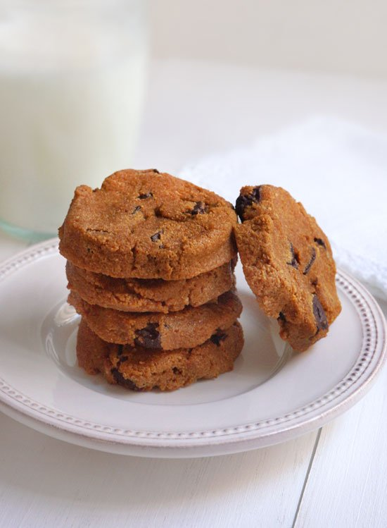pumpkin chocolate chip cookies stacked on a plate