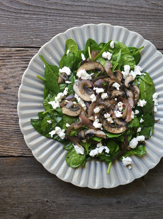 warm mushroom and spinach salad on a plate with goat cheese on top