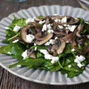 Close up of warm mushroom and spinach salad topped with cheese