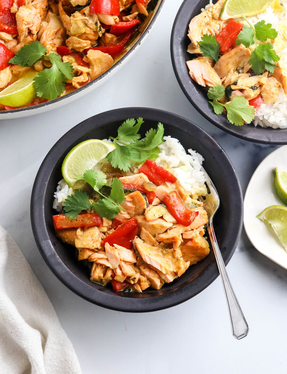 salmon curry over rice in black bowl