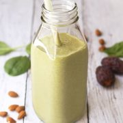 almond butter and spinach shake in glass jar with straw