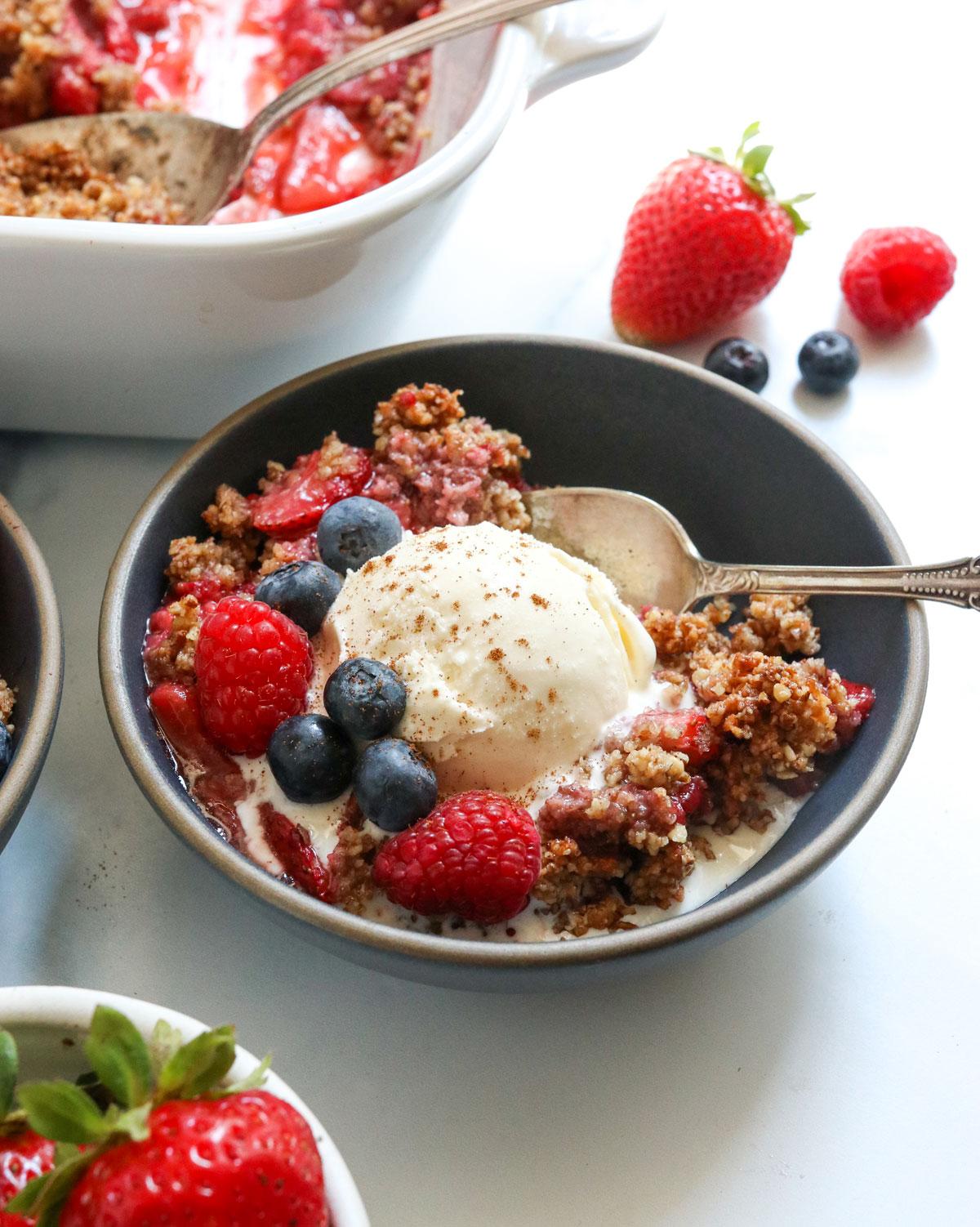 paleo berry crisp in dark bowl with ice cream