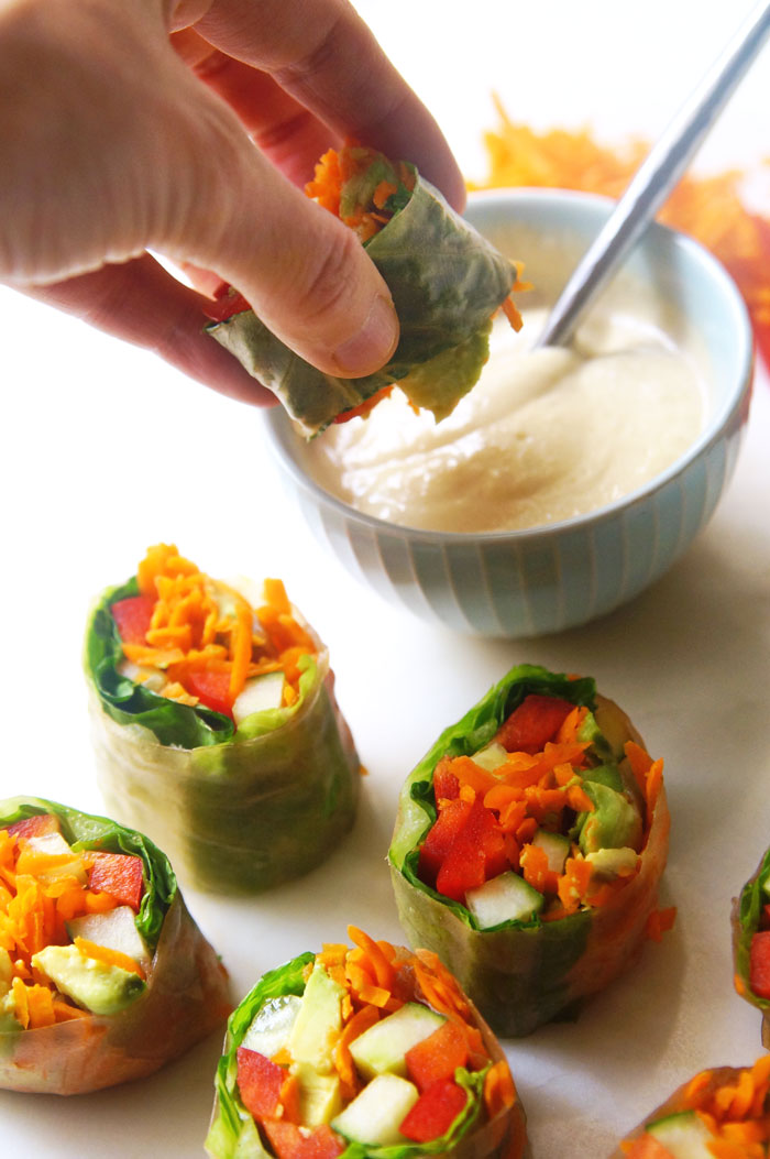 hand dipping a vegetable salad roll into the dipping sauce