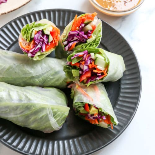 spring rolls on black plate with peanut sauce