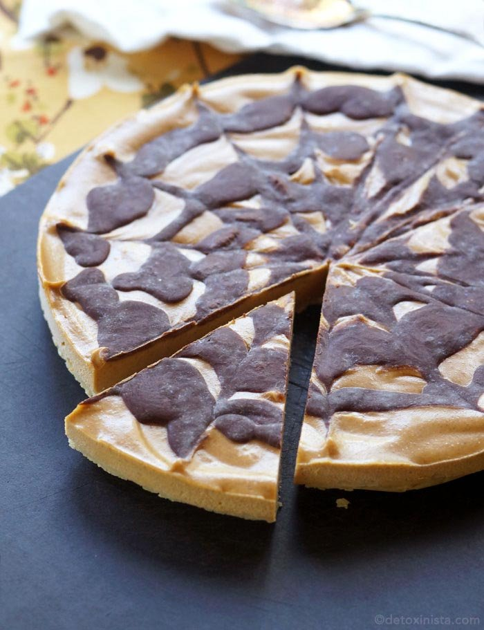 pumpkin chocolate cheesecake with a slice cut out of it