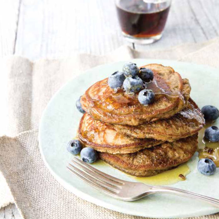 blender banana pancakes stacked on a plate with blueberries and syrup on top