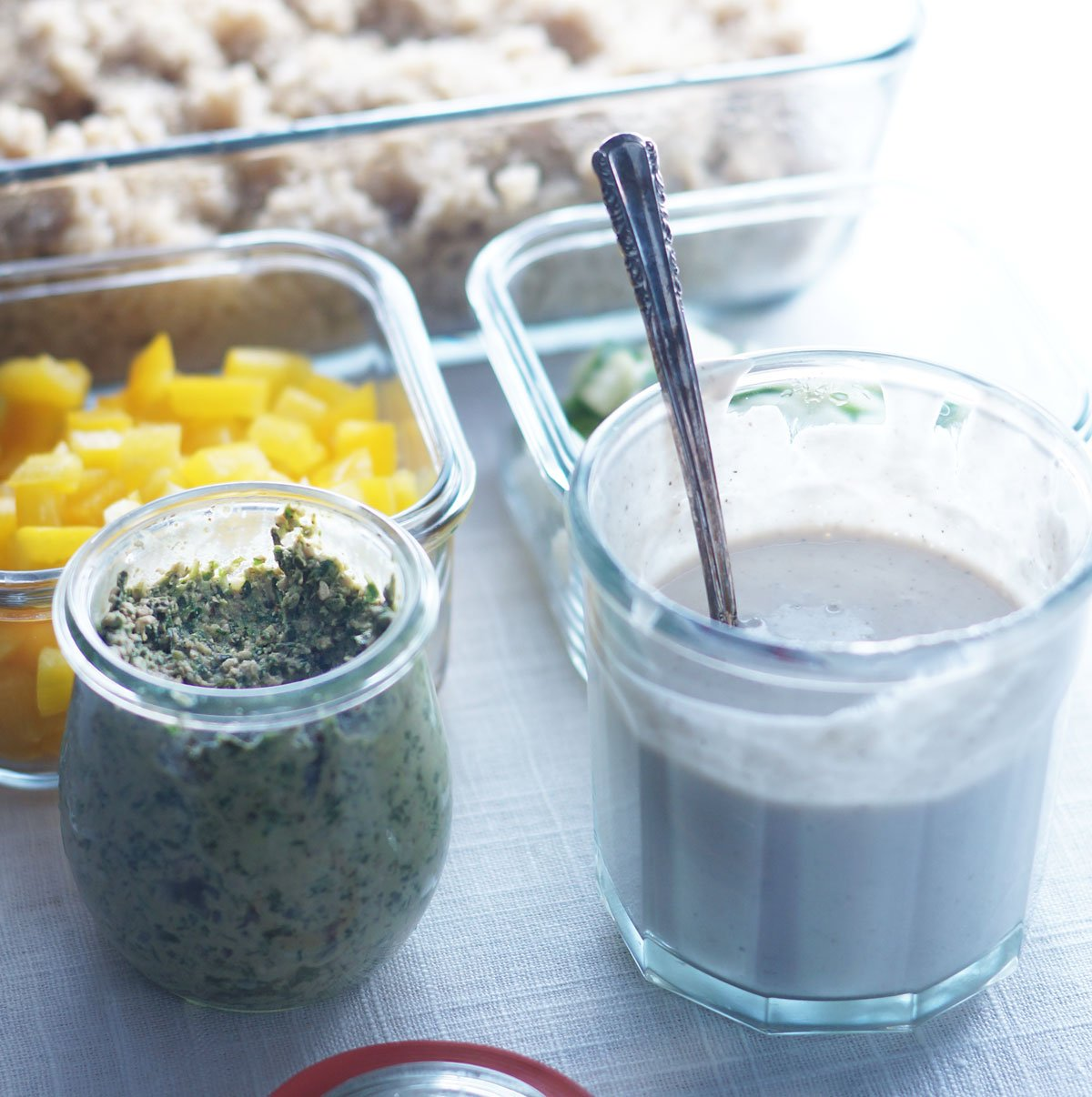 small glass jars with dressing for vegan lunch bowls