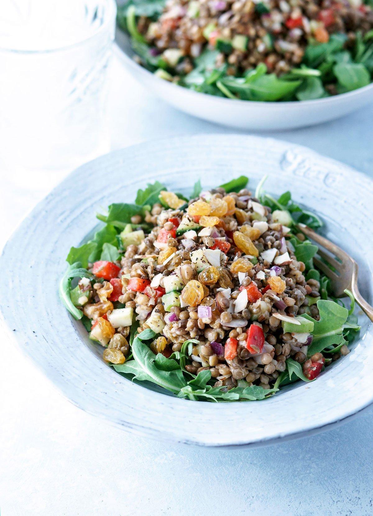 bowl of lentil potluck salad with a fork