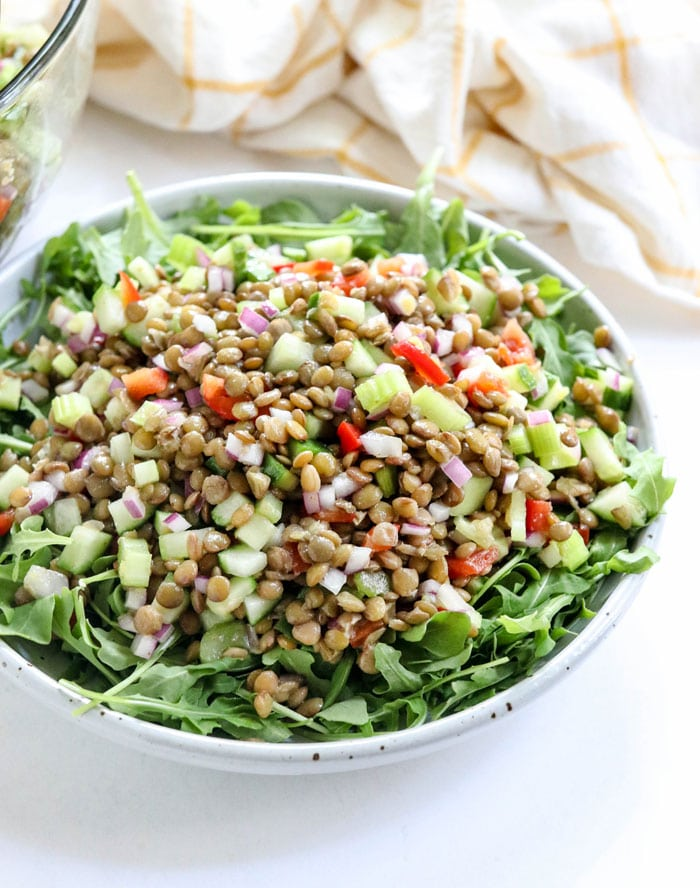 lentil salad over a bowl of arugula