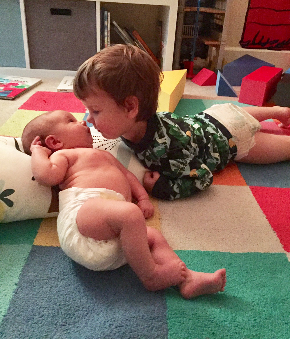 baby and toddler laying on the floor