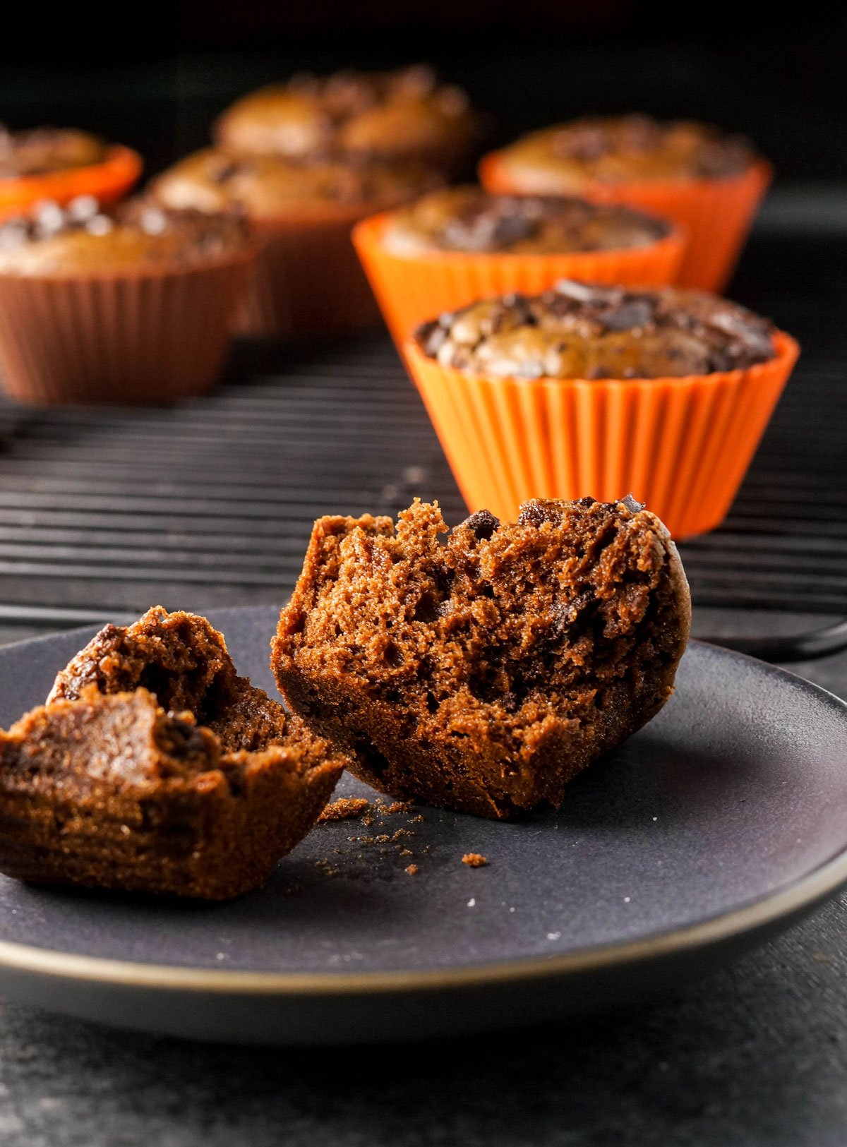 double chocolate pumpkin muffin broken in half on a plate
