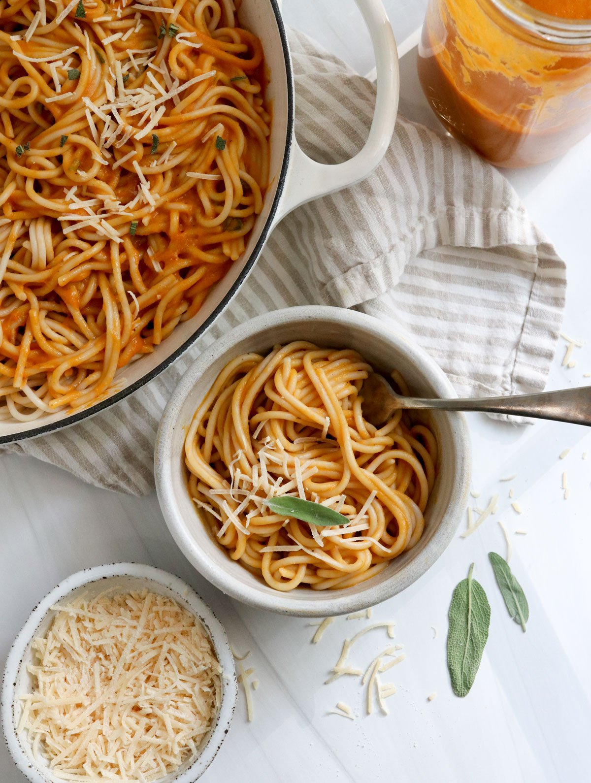 bowl of pumpkin pasta next to a white skillet