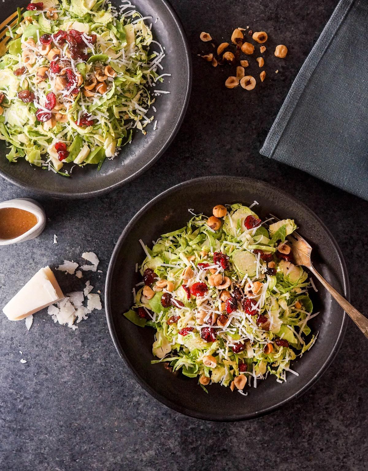 two bowls of brussels sprout salad with dried cranberries on top