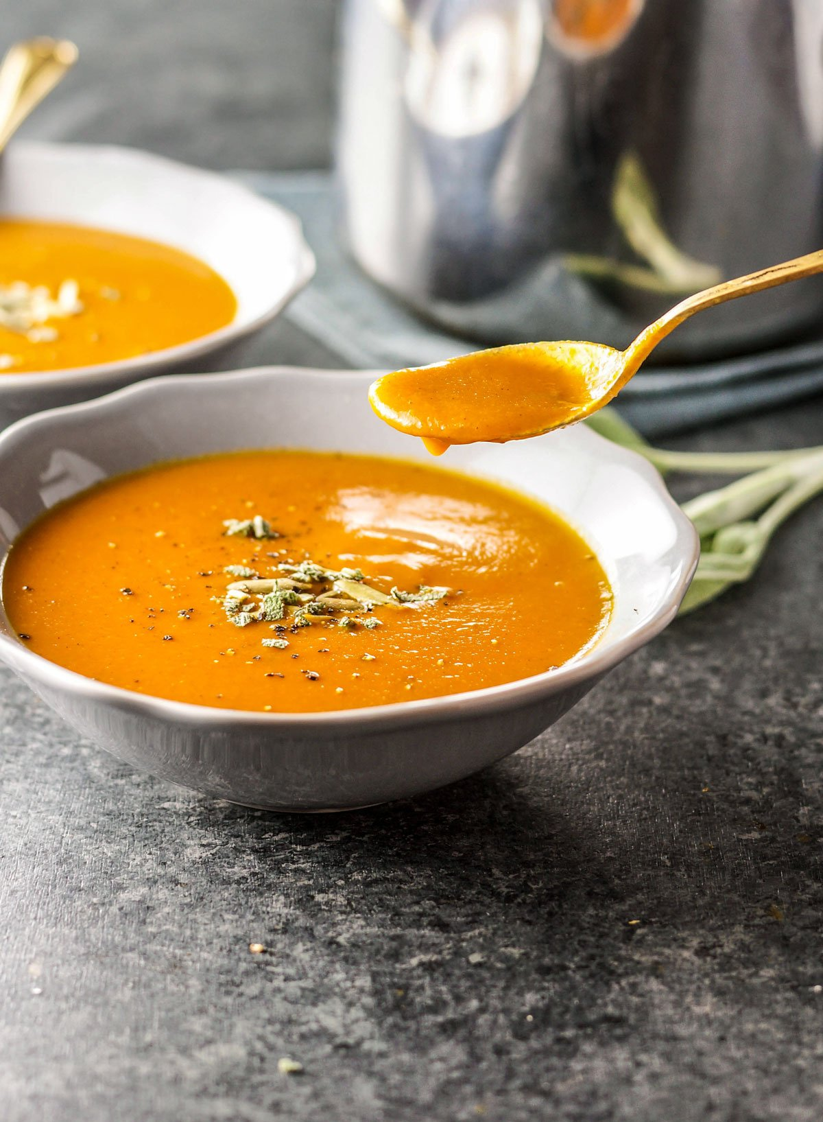 bowl of creamy pumpkin tomato soup with a spoon