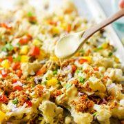 spoon drizzling sauce on vegan cauliflower nachos