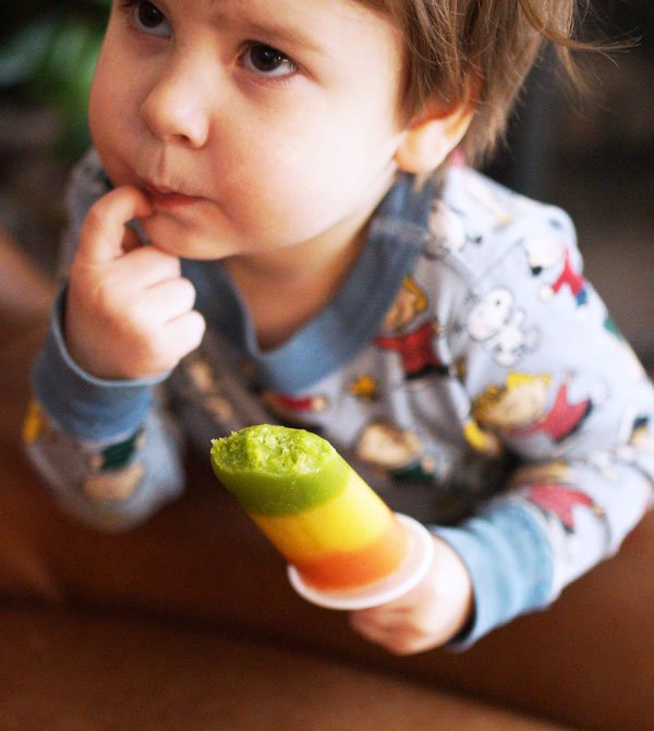 toddler eating a healthy layered popsicle
