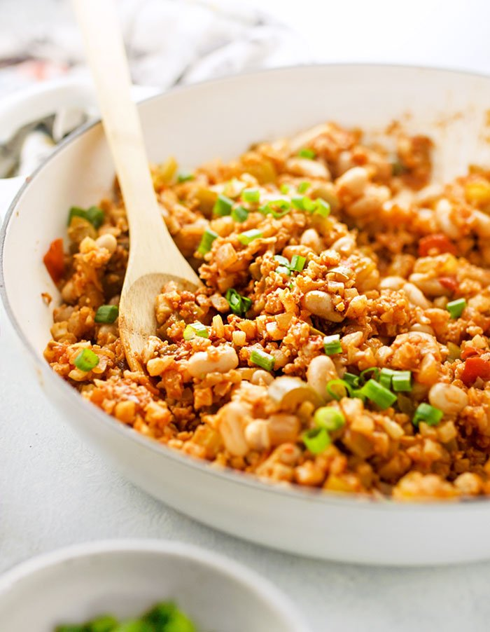 pan of Healthy Creole-Style Cauliflower Rice Jambalaya with a wooden spoon