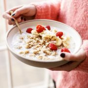 overhead quinoa breakfast bowl with raspberries held by woman