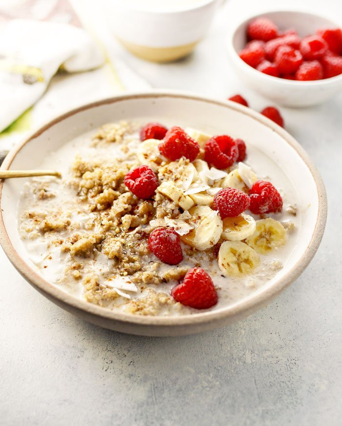 detox quinoa breakfast bowl with raspberries and bananas on top