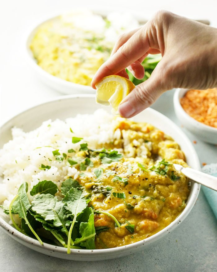 hand squeezing lemon over a bowl of red lentil and kale curry
