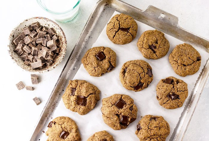 buckwheat chocolate chip cookies on a cookie sheet with a bowl of chocolate chunks next to it