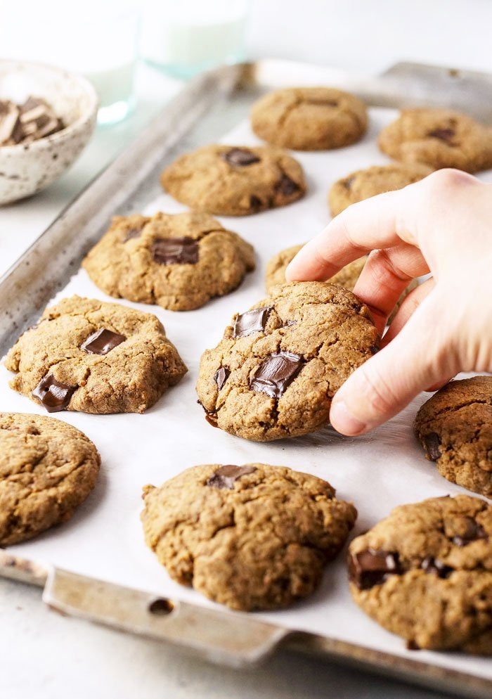 hand picking up a buckwheat chocolate chip cookie from a pan